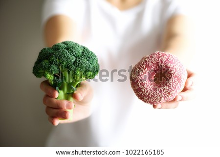 Young woman in white T-shirt choosing between broccoli or junk food, donut. Healthy clean detox eating concept. Vegetarian, vegan, raw concept. Copy space.