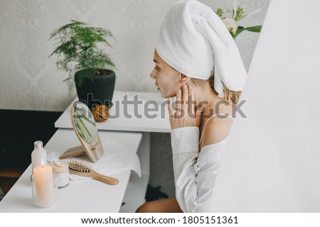 Young woman in white towel chilling in bedroom and making clay facial mask near mirror. Girl doing beauty treatment and relaxing at home. Morning skin care beauty routine, self care.