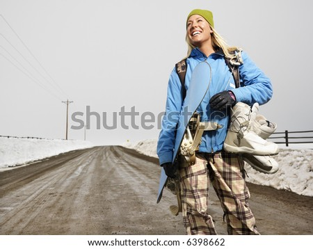 Young woman in winter clothes standing on muddy dirt road holding snowboard and boots smiling.