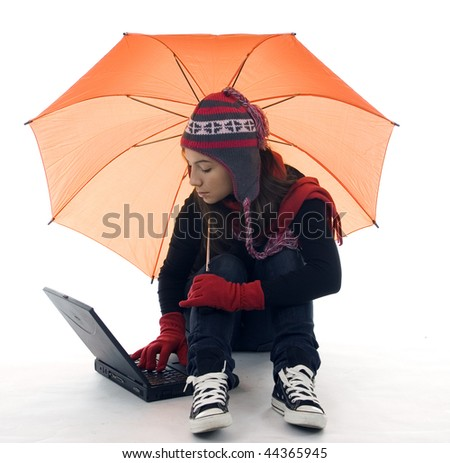 young woman in winter clothes with umbrella working on laptop