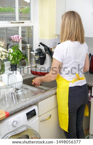 Young Woman in yellow apron washing dishes and cleaning kitchen. Housekeeper washes pate in sink. Domestic life