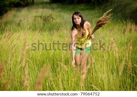 Young woman in yellow clothes enjoying picking wild flowers in a green field.