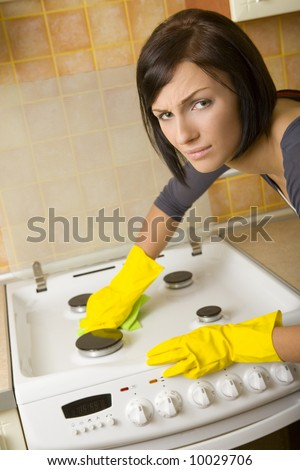 Young woman in yellow rubber gloves cleaning cooker. Looking at camera. Front view.