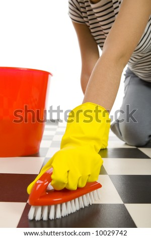 Young woman in yellow rubber gloves kneeling and scrubs the floor. Closeup on hand in glove with brush.