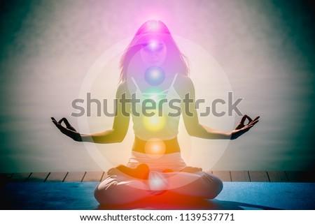 Young woman in yoga meditation hands with seven chakras and Yin Yang symbols.