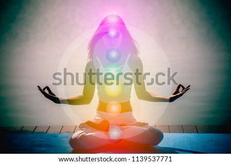 Young woman in yoga meditation with seven chakras and Yin Yang symbols.