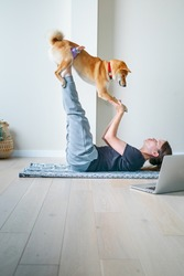 Young woman in yoga position balancing with her dog. Home online training with a pet. Doga or Doga yoga is the practice of yoga as exercise with dogs