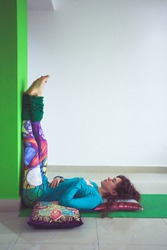 young woman in yoga relaxing pose with legs up the wall side view indoor