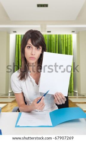 Young woman in zen interior pointing with her pen to a blank paper. Ideal for inserting your own message