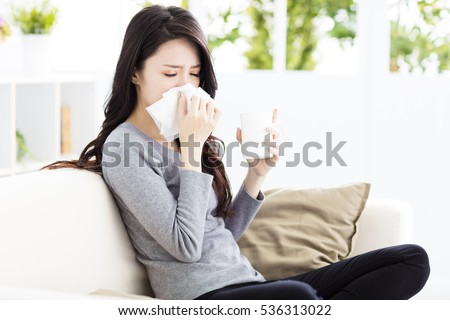 Young Woman Infected With Cold Blowing Her Nose