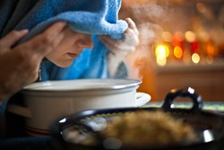 Young woman inhaling chamomile tea steam as an alternative therapy or traditional cure.