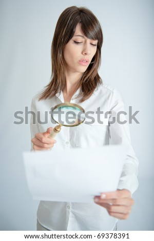 Young woman inspecting closely a document through a magnifying glass