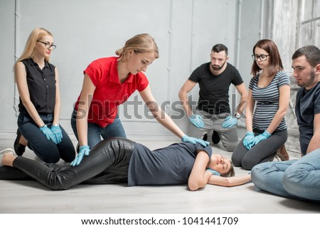 Young woman instructor showing how to lay down a woman during the first medical aid training indoors Stock photo ©