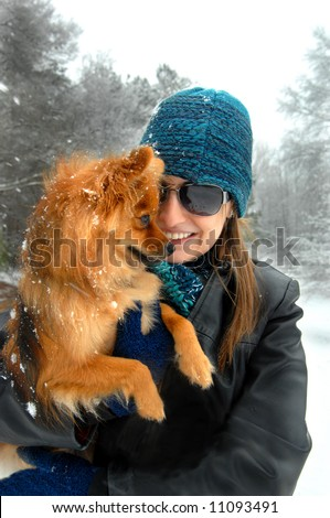 Young woman introduces her Pomeranian puppy to its first snow. Leather jacket and blue knit cap.