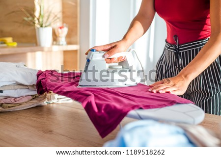 Young woman ironing clothes. Close up hand of woman ironing clothes on the table. Closeup of woman ironing clothes on ironing board. Household duties, taking care of clothes concept.