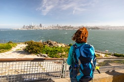Young woman is admiring San Francisco  cityscape from Alactraz island in San Francisco, United States of America.