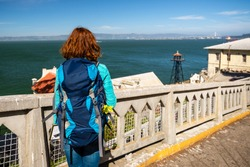Young woman is admiring the view from Alcatraz island in San Francisco Bay, United States of America