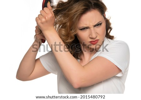 Young woman is angry with her knotty hair, isolated on white. Stock photo ©
