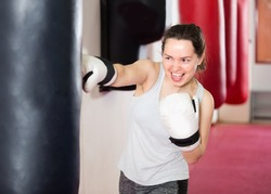 Young woman is beating a boxing bag in the boxing hall.