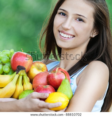 young woman is beautiful healthy wields lot of fruit