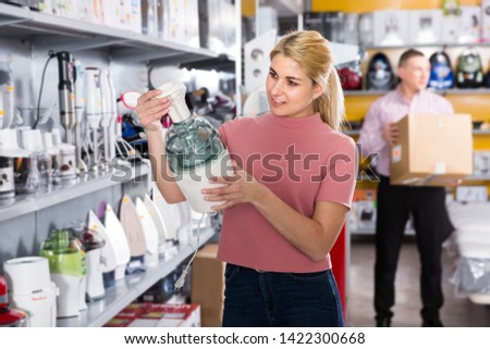 Young woman is choosing blender for his kitchen in appliances store