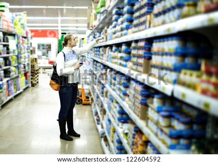 Young woman is choosing food for her child at the food store. Wide shot, shallow dof.