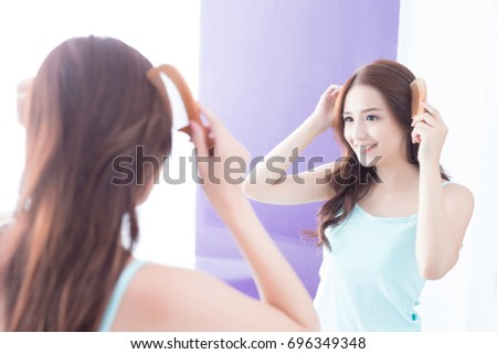 young woman is combing hair in bathroom at home