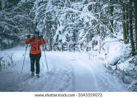 Young woman is cross-country skiing while snowing. Active winter. Active recreation. Active life. #1043359072