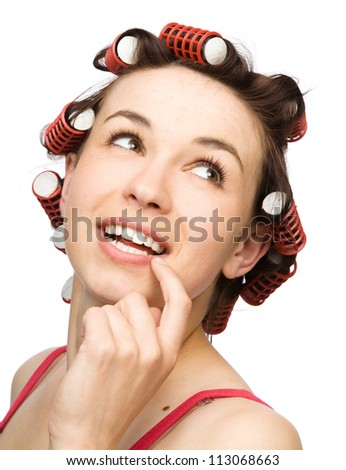 Young woman is daydreaming while wearing hair rollers, isolated over white