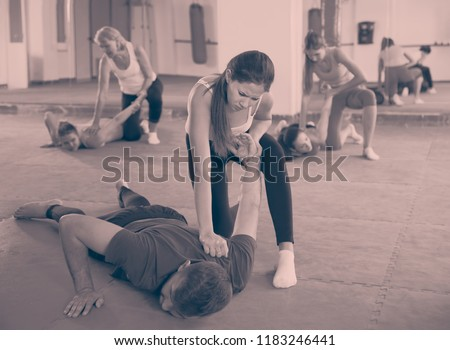 Young woman is doing self-defence moves with trainer in sporty fitness club Stock photo ©