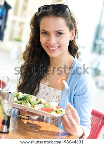 Young woman is eating mixed vegetable salad in cafe
