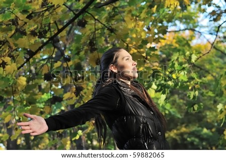 Young woman is enjoying her life outdoors among trees on sunny autumn day