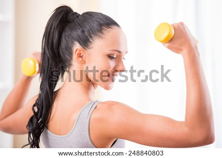 Young woman is exercising with dumbbells at home. Fitness, workout, healthy living and diet concept.