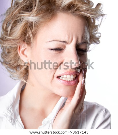Young woman is having toothache isolated on white