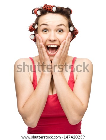 Young woman is holding her face in astonishment while wearing hair-rollers, isolated over white - stock photo