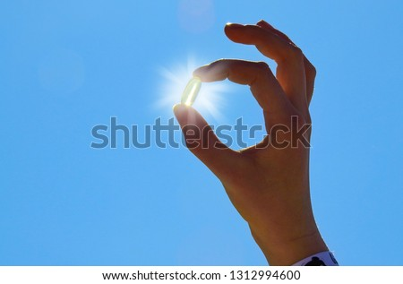 Young Woman is holding Vitamin D Capsule