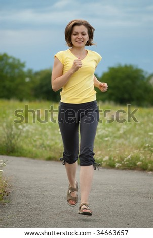 Young woman is jogging in city park