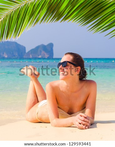 young woman is lying on beach