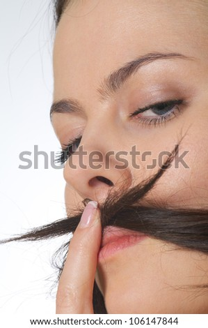 young woman is making a moustache of her hair