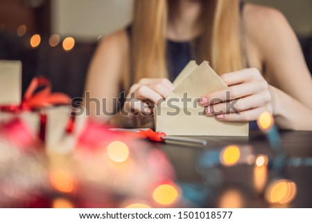 Young woman is packing presents. Present wrapped in craft paper with a red and gold ribbon for christmas, birthday, mother's day or valentine