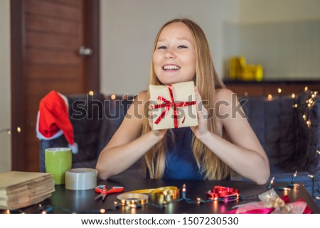 Young woman is packing presents. Present wrapped in craft paper with a red and gold ribbon for christmas or new year. Woman makes an advent calendar for her child