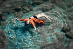Young woman is posing in red chemise in clear blue sea water on surface