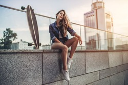 Young woman is posing with skateboard in the city. Female teenager outdoor with long board.