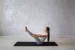Young woman is practicing yoga. Boat Pose Variation. Navasana