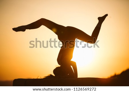 Young woman is practicing yoga on the mountain at sunset. Silhouette of young woman practicing yoga outdoor. #1126569272