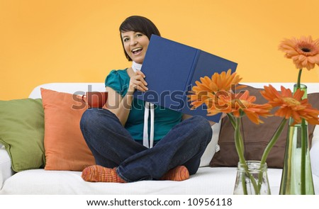 young woman is reading a book on a sofa