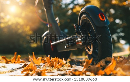 Young woman is ready to discover the urban city in autumn at sunset with electric scooter or e-scooter, Electric urban transportation concept image