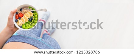 Young woman is resting and eating a healthy oatmeal after a workout.