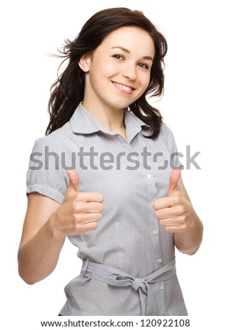 Young woman is showing thumb up gesture using both hands, isolated over white