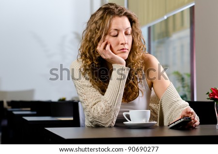 young woman is sitting at cafe and waiting for someone